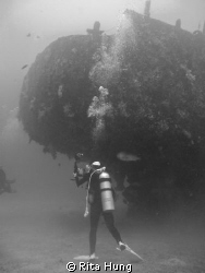 Diver so concentrate to take photograph of the ship wreck. by Rita Hung 
